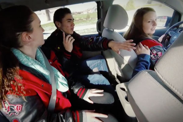 a group of teens in a car talking to each other