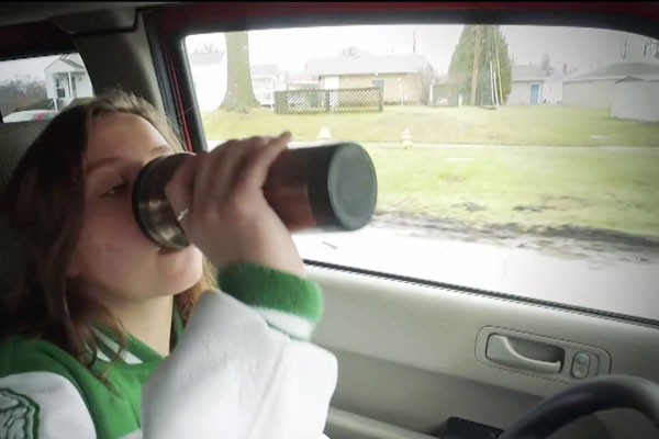 a teen girl driving while drinking out of an insulated travel cup