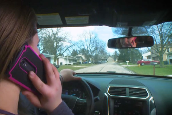 backseat view of a girl driving while on her cell phone