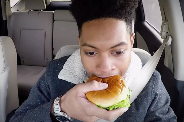 a teen eating a sandwich while driving