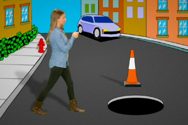 teen walking toward a manhole while texting on her cell phone