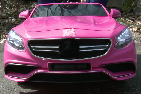 a close up of the front of a pink car