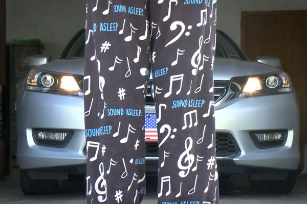 back of a persons legs in sleepy pajamas standing in front of a car