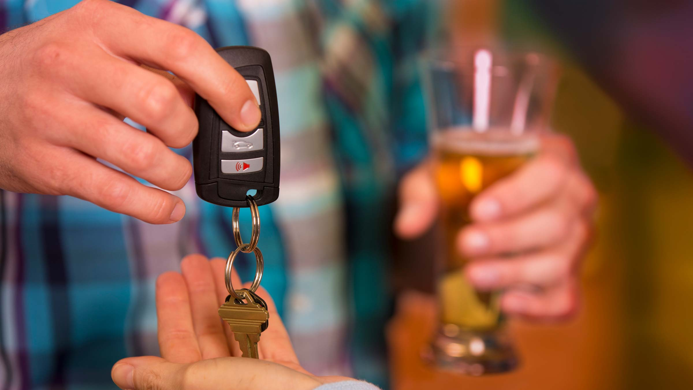 man drinking and handing over his car keys