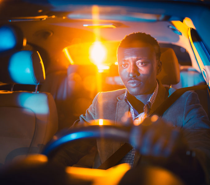 man driving at night looking tired