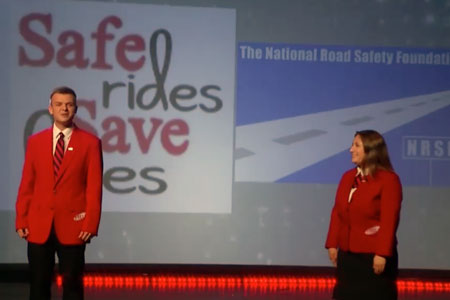 Two FCCLA representatives on a stage with the safe rides save lives logo