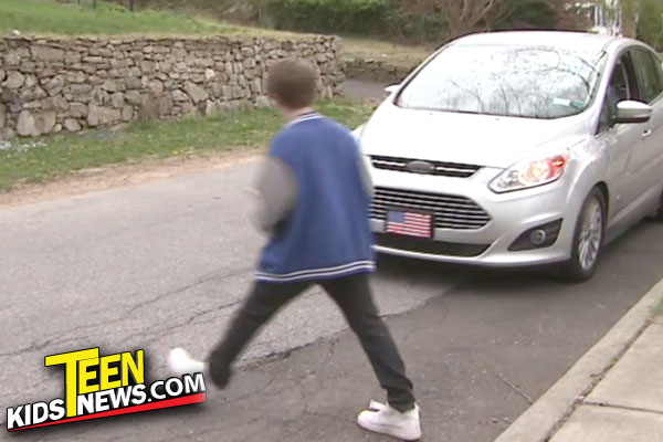 kid walking across the street with a car coming