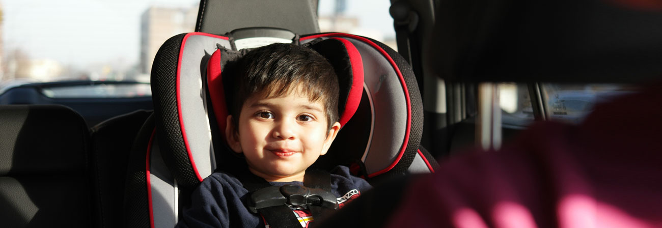 a young child in a carseat in the back of a car