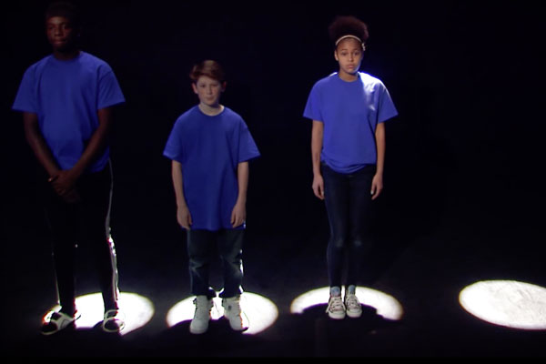 three teens standing in lighted spots on the floor in a black room