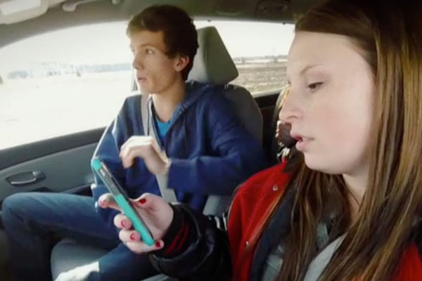 close up of teens in a car, with the girl behind the wheel texting