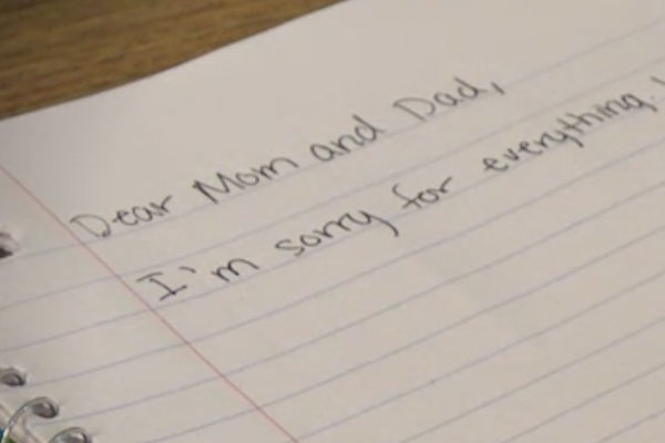 "close up of a ruled notebook with ""dear mom and dad"""