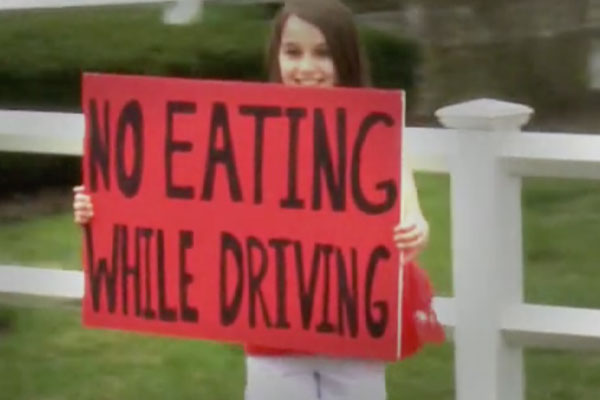 "a young girl on the side of the road holding up a sign that says ""no eating while driving"""