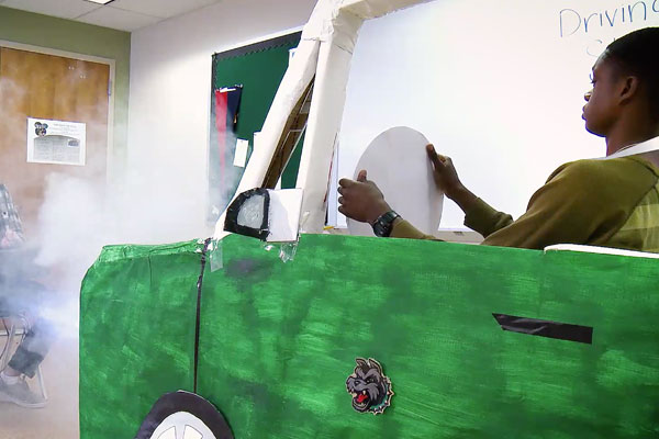 a boy driving in a green car made of cardboard with fog being blown at him