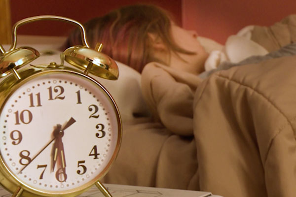 an alarm clock and a person sleeping
