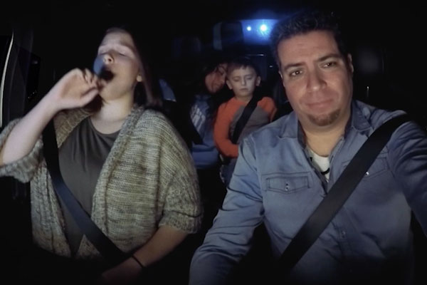 a family in a car driving at night and tired