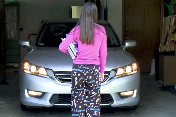a teen girl in a pink shirt and sleep pajamas standing in front of a car