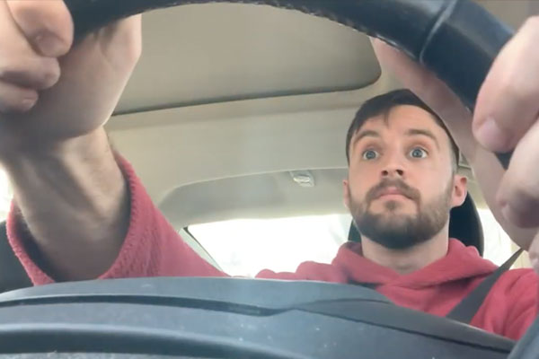 under view of a man holding a steering wheel