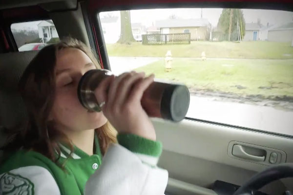a girl drinking coffee in a car