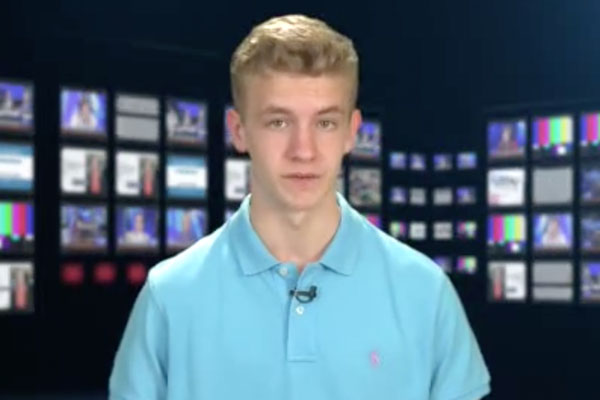 a teen anchor in a blue shirt with a monitor background
