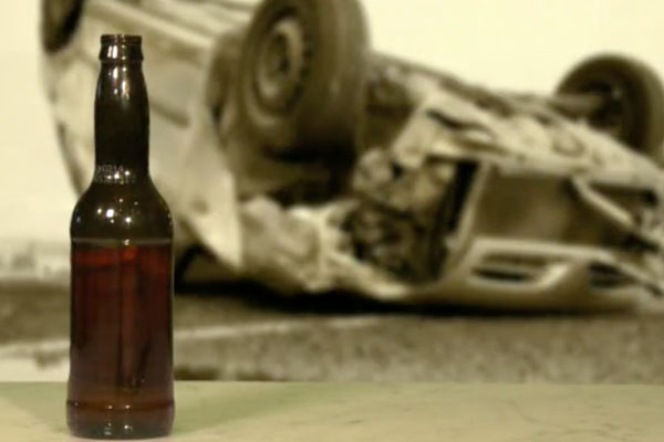 car overturned with a beer bottle in the foreground