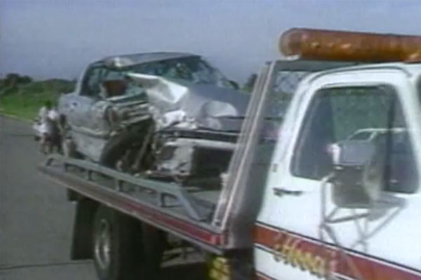 a platform tow-truck carrying a crashed car