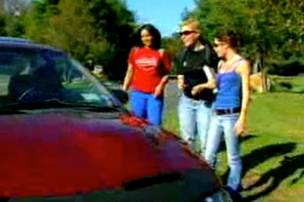 3 women standing next to a red sports car