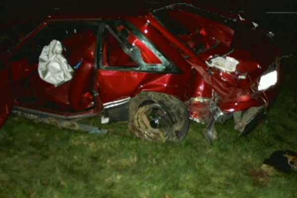 a destroyed red car on the grass after it crashed